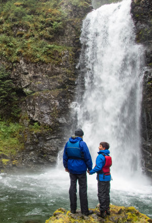 Father and son stand in front of waterfall