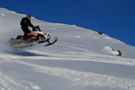 Snowmobiling over mountain