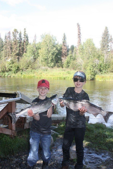 Kids holding fresh caught Silver Salmon